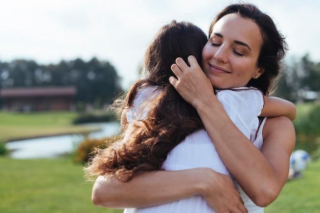 Mãe amorosa, abraçar, filha, ao ar livre