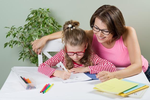 Mãe amorosa, ajudando a filha a escrever o aluno da escola primária