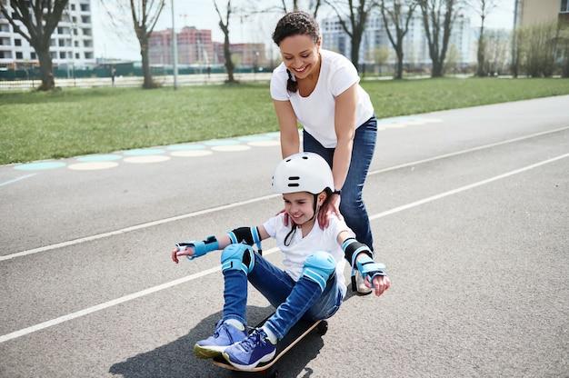 Mãe amorosa atrás de seu filho, que está sentado em um skate