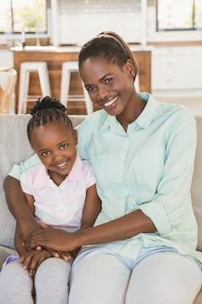 Mãe amorosa com a filha no sofá na sala de estar