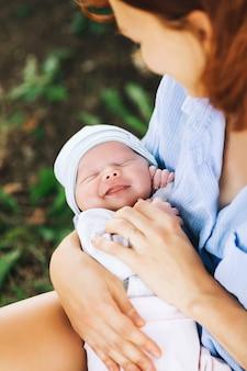 Mãe amorosa com seu bebê recém-nascido nos braços linda mãe com filho recém-nascido na natureza