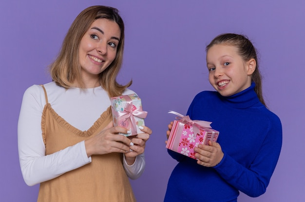 Mãe amorosa e filha feliz segurando presentes