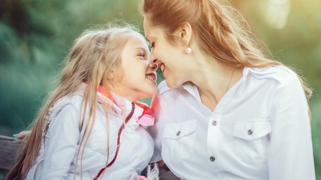 Mãe amorosa e filha relaxando no parque