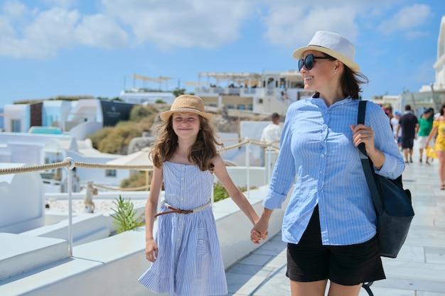 Mãe andando com a criança filha segurando a mão na famosa vila turística de oia ilha de santorini. mulher e menina felizes em um dia ensolarado de verão caminhando juntas, copie o espaço