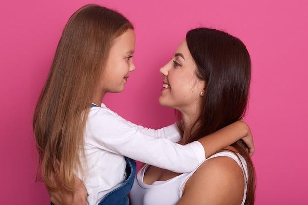 Mãe animada e garota garoto bonito olhando uns aos outros com sorrisos encantadores, vestindo camisas brancas, cabelos longos, posando isolado sobre rosa