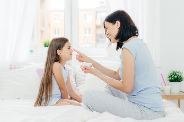 Mãe aplica creme no nariz da filha, senta-se juntos na cama, leva bolo de pele saudável e boa aparência