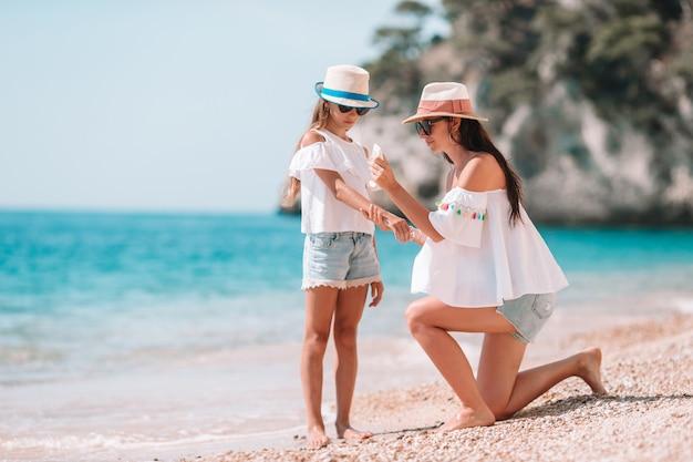 Mãe, aplicando, creme proteção sol, para, dela, filha, em, praia tropical