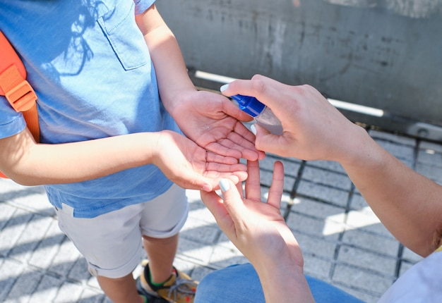 Mãe aplicando gel desinfetante para as mãos nas mãos do filho antes de entrar na escola