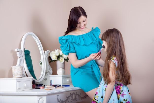 Mãe aplicando maquiagem em sua linda filha pré-adolescente em casa.