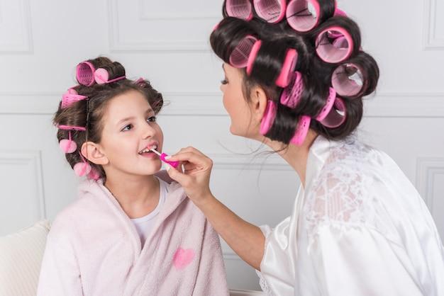 Mãe, aplicando o batom rosa nos lábios da filha
