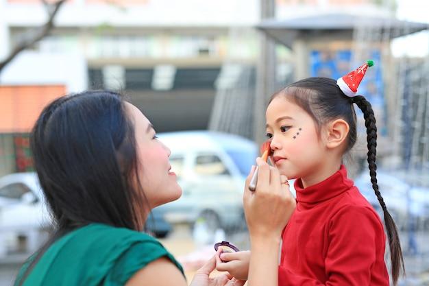Mãe, aplicar maquiagem no rosto da filha.