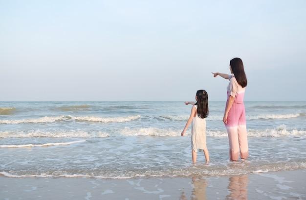 Mãe apontando algo com uma menina criança olhando para o mar
