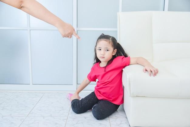 Mãe apontando o dedo para a filha enquanto repreende a filha em casa