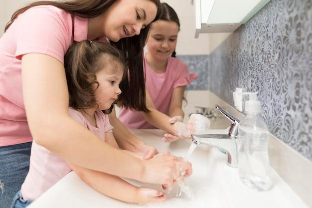 Mãe aprendendo menina a lavar as mãos