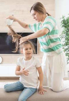 Mãe arruma o cabelo da filha. menina não quer ter o cabelo penteado. feche a foto. criança se sente mal, porque a mãe puxa o cabelo dela