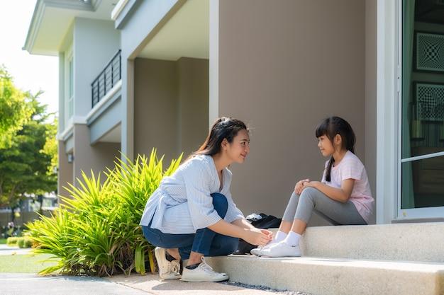 Mãe asiática ajuda a filha a amarrar cadarços