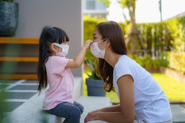 Mãe asiática ajuda a filha com máscara de proteção