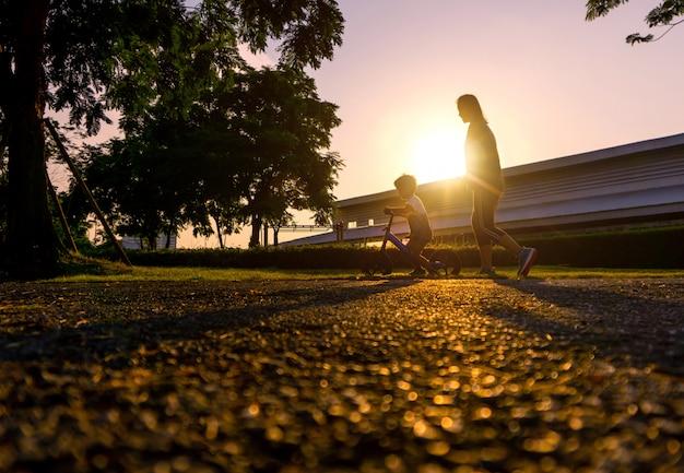 Mãe asiática ajuda seu filho a andar de bicicleta