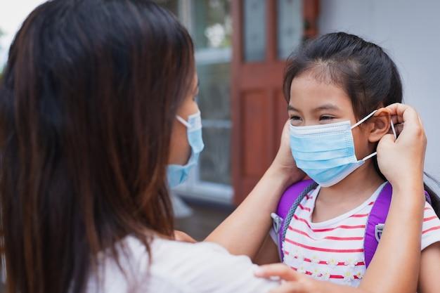 Mãe asiática ajudando sua filha com máscara médica antes de sair para se proteger da situação de surto do vírus covid-19 como novo estilo de vida normal. conceito de saúde e distância social.
