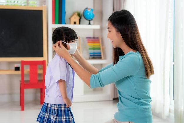Mãe asiática ajudar a filha usando máscara médica