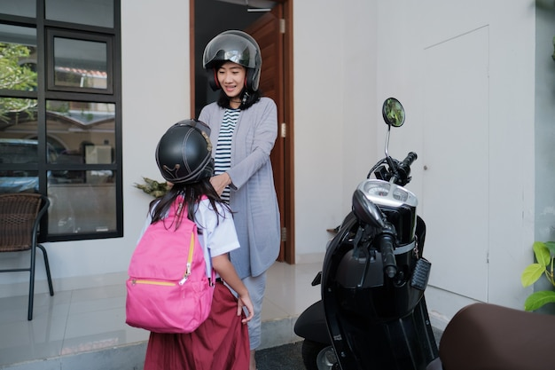 Mãe asiática apertar o capacete da filha. levando para a escola de scooter de motocicleta pela manhã. aluno primário voltando para a escola
