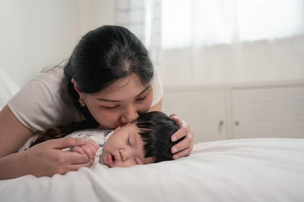 Mãe asiática beijando e tocando um bebê que dorme na cama com suavidade e amor