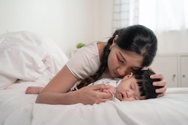Mãe asiática beijando e tocando um bebê que dormindo na cama com delicadeza e amor, sentindo-se feliz.