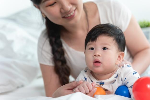 Mãe asiática bonita nova com o bebê asiático na cama e jogando a bola do brinquedo junto na cama branca com sentimento feliz e alegre e o bebê que rastejando na cama. conceito de família do bebê