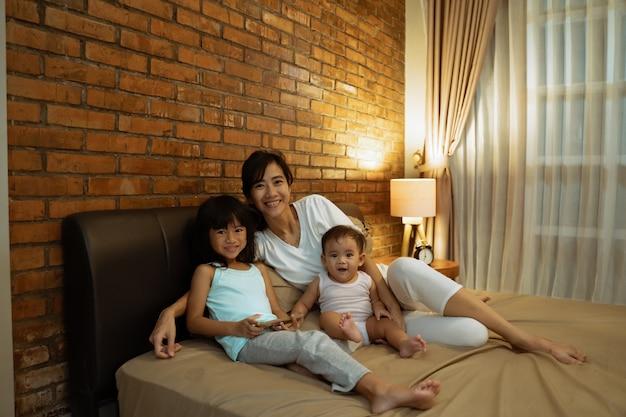 Mãe asiática brincando com as filhas na cama