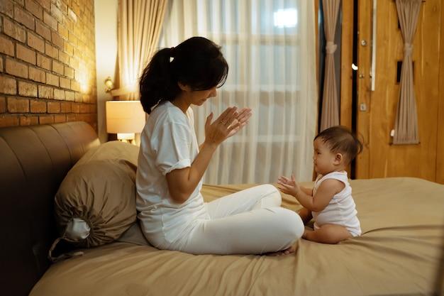 Mãe asiática brincando com seu bebê na cama