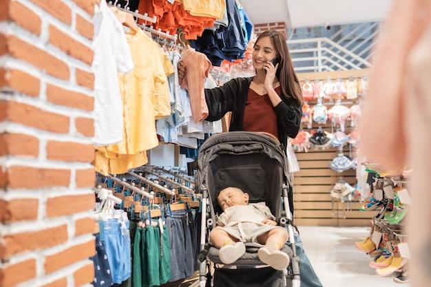 Mãe asiática com filho fazendo compras no shopping enquanto liga para o telefone