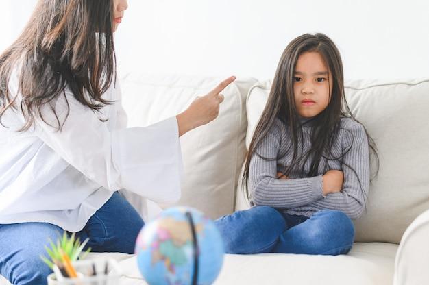 Mãe asiática com raiva, sentada com a filha pequena, mãe repreende a criança caprichosa de mau comportamento de disciplina.
