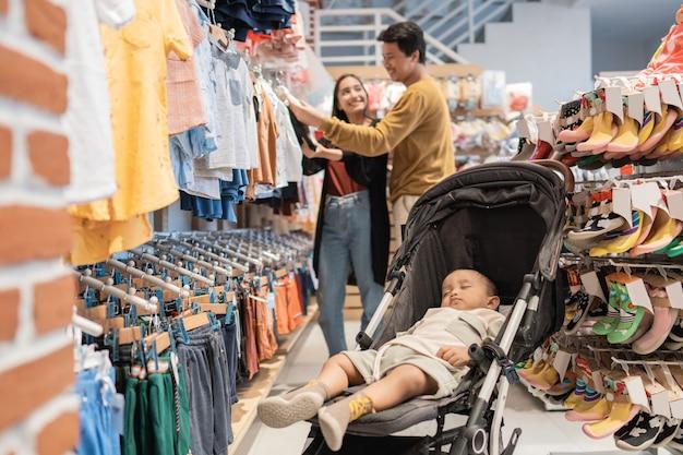 Mãe asiática com seu filho pequeno fazendo compras na loja de bebês