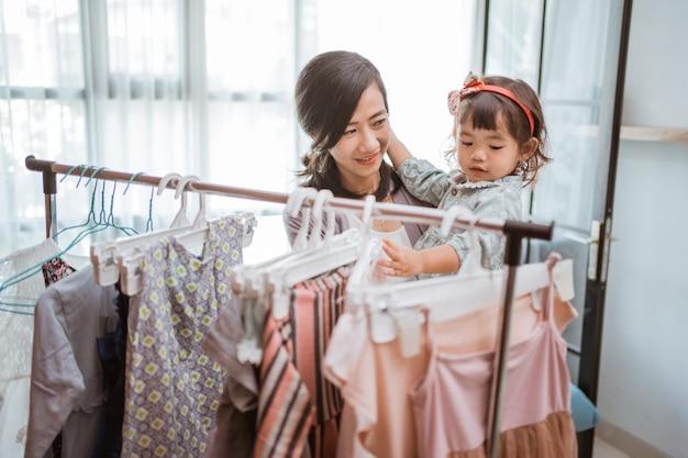Mãe asiática comprando roupas enquanto faz compras com seu bebê