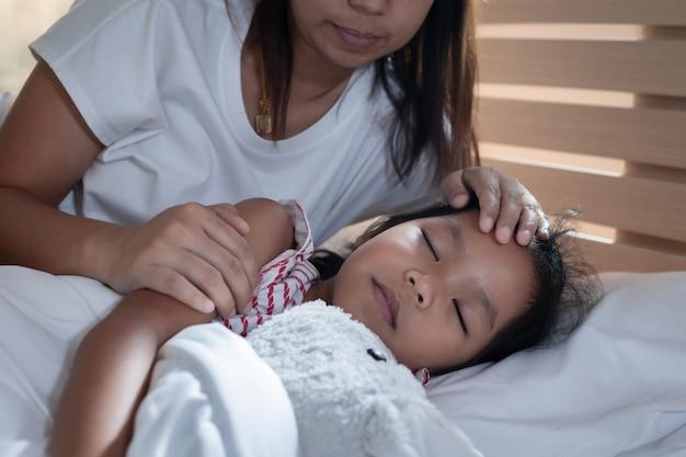 Mãe asiática cuida de sua filha doente enquanto ela está abraçando a boneca e dormindo na cama