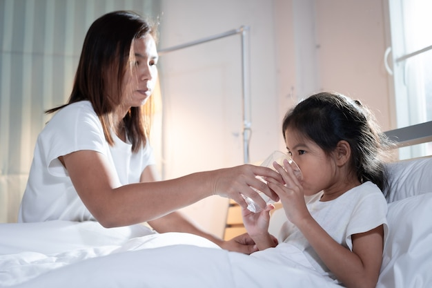 Mãe asiática dando copo d'água para menina criança doente depois de comer remédio no quarto