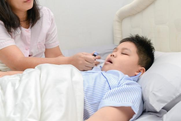 Mãe asiática dando xarope de filho por causa da gripe no quarto