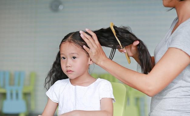 Mãe asiática de close-up, penteando o cabelo da filha em casa.