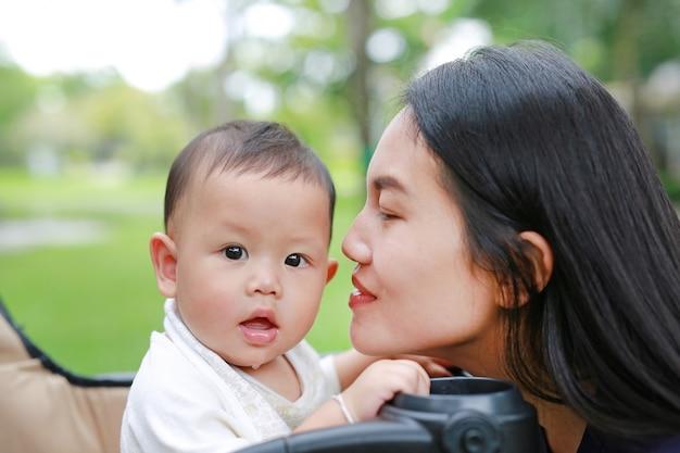 Mãe asiática do close-up e seu bebê no trole no parque.