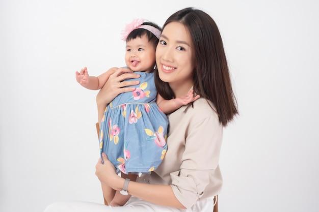 Mãe asiática e adorável menina estão felizes na parede branca