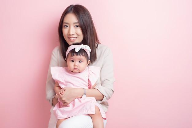 Mãe asiática e adorável menina estão felizes na parede rosa