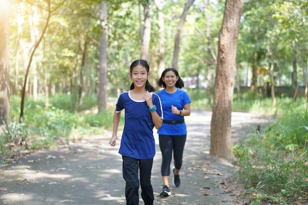 Mãe asiática e filha que movimentam-se em um parque.