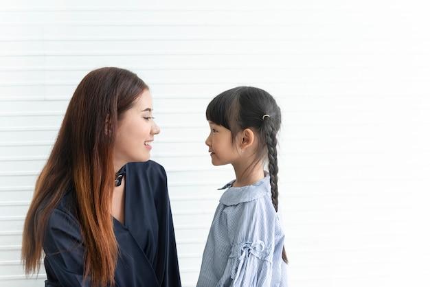 Mãe asiática e filha que olham o olho junto na sala de visitas em casa.
