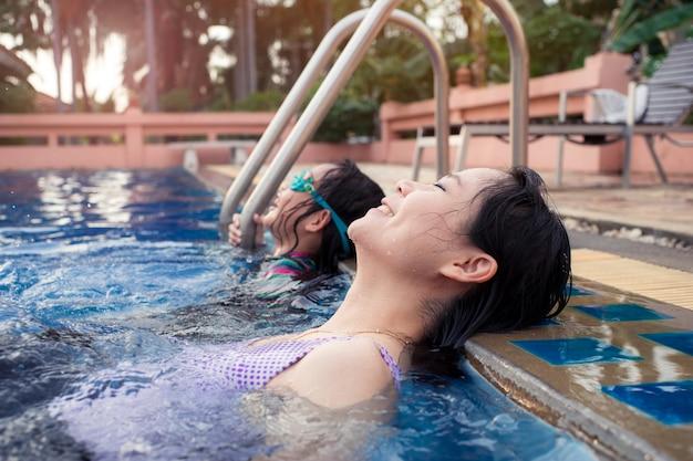 Mãe asiática e filha que relaxam na piscina com felicidade e emoções.
