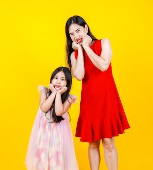 Mãe asiática e filha tirando foto do retrato juntos em fundo amarelo com engraçado e adorável.