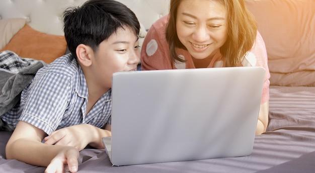Mãe asiática e filho da família que olham no computador portátil.