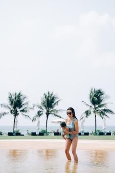 Mãe asiática e filho pequeno, desfrutando de um mergulho em uma piscina nas férias de verão.