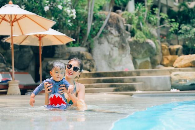 Mãe asiática e filho pequeno nadando em uma piscina nas férias de verão