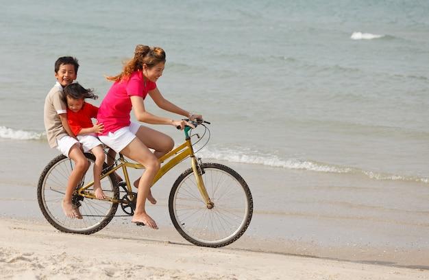 Mãe asiática e filhos andando de bicicleta em praia tropical