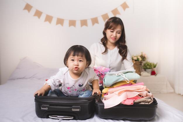 Mãe asiática e menina com bagagem de mão e roupas prontas para viajar de férias